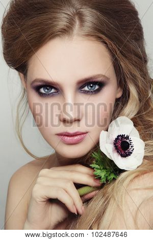 Portrait of young beautiful girl with stylish violet smoky eyes make-up and messy hairdo