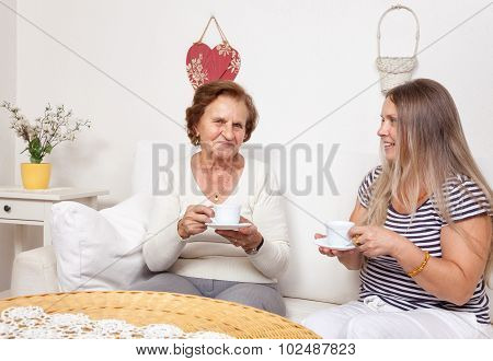 Carer Having A Cup Of Tea With An Elderly Woman