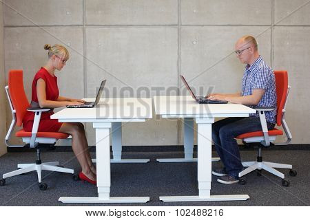 middle-aged man and young woman working in correct sitting posture with laptops at electric height adjustable desks in office