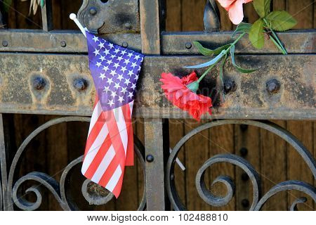 Small flag and flower on rusty door