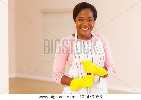 portrait of beautiful young black woman cleaning her new home