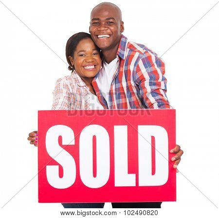 cheerful african couple showing sold sign