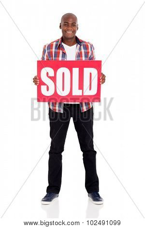 happy young african man holding a sold sign against white background