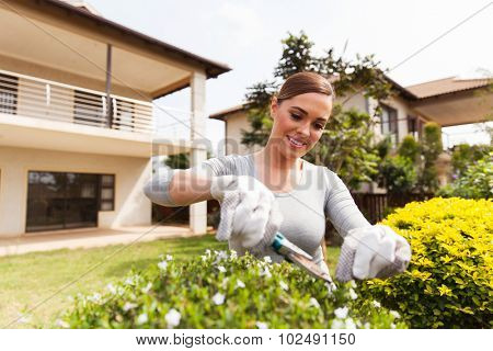 pretty young woman cutting plants in home garden