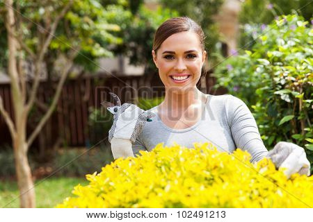 portrait of beautiful young woman gardening at home