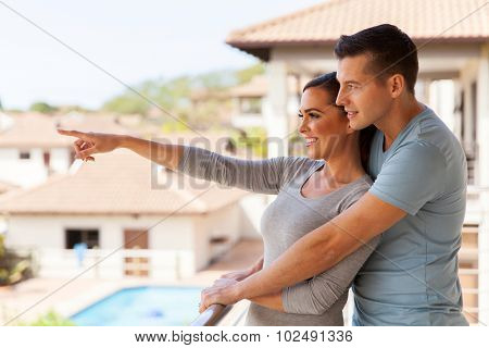 happy young couple relaxing on balcony at home