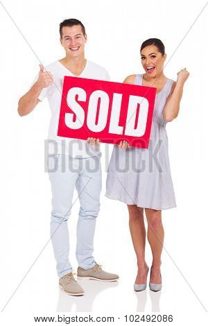 cheerful young couple holding a sold sign on white background