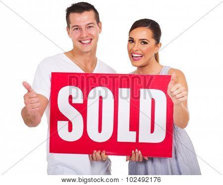 happy couple holding sold sign and giving thumbs up