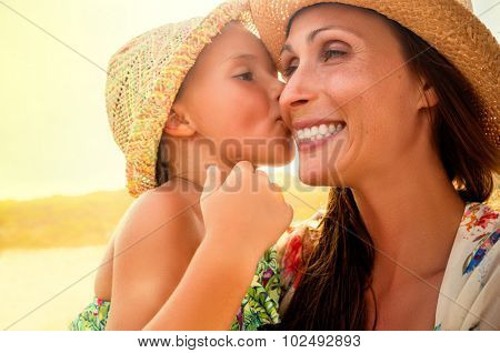 mothers love daughter kissing on sunny day
