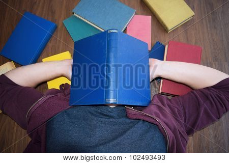 Man Lying On The Floor With A Book On His Face