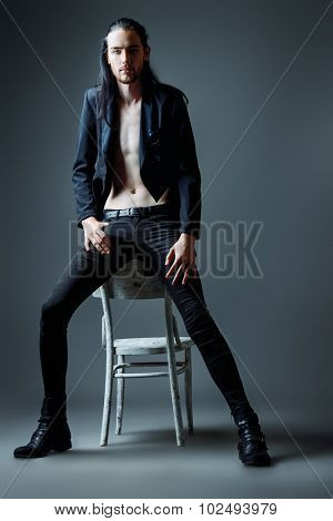 Vogue style photo of a handsome man in black clothes. Men's fashion, beauty.