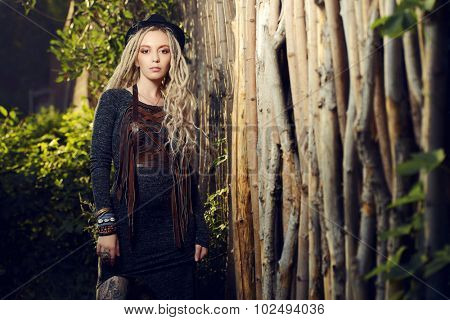 Attractive young woman wearing clothes in boho style posing by a wooden fence.