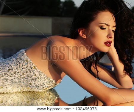 Woman With Dark Hair In Luxurious Sequin Dress Lying On Mirror