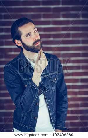 Thoughtful handsome with hand on chin man looking away against wall