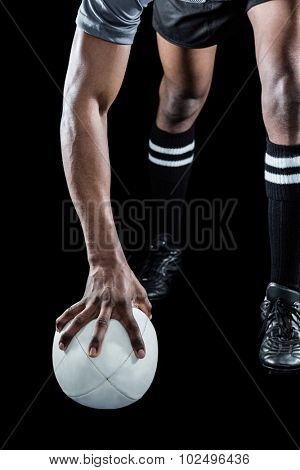 Low section of athlete holding rugby ball over black background