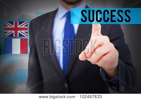The word success and businessman pointing his finger at camera against abstract grey room