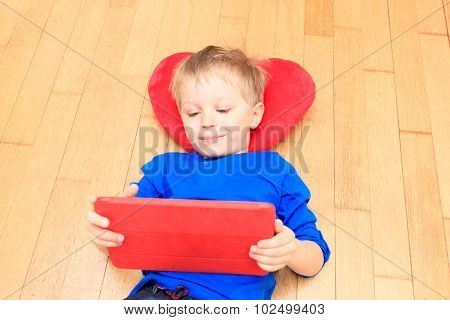 little boy looking at touch pad, early learning