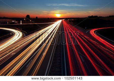 Speed Traffic light trails on highway at sundown time, long exposure, urban background with sun and dark sky