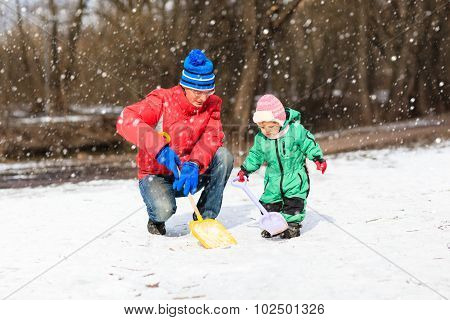 father and little daughter digging snow in winter park