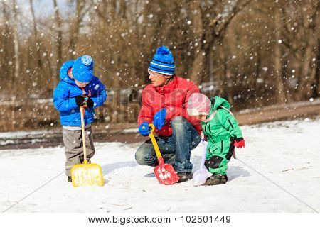 father and kids digging snow in winter park