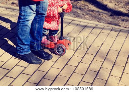 mother teaching little daughter to ride scooter
