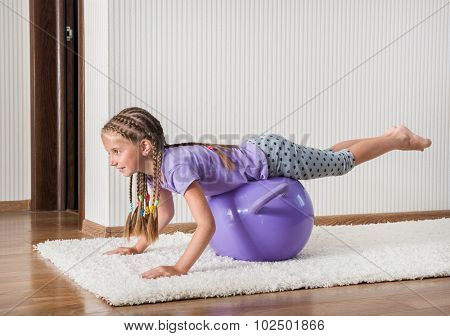 smiling girl with african braids on the ball for fittnesa at home
