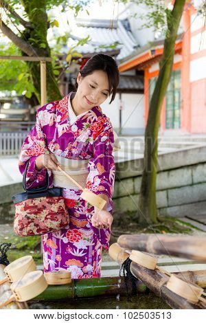 Young japanese woman use of the bamboo ladle in water fountain