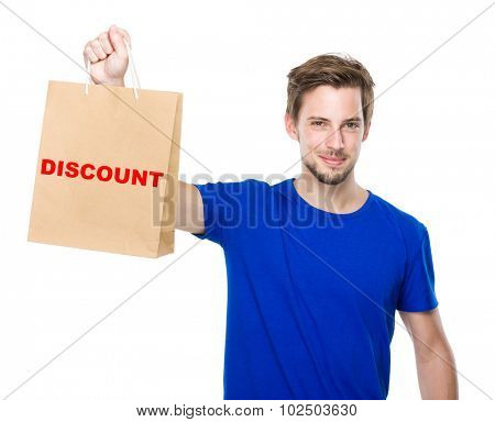 Young man hold with shopping bag and showing a word discount
