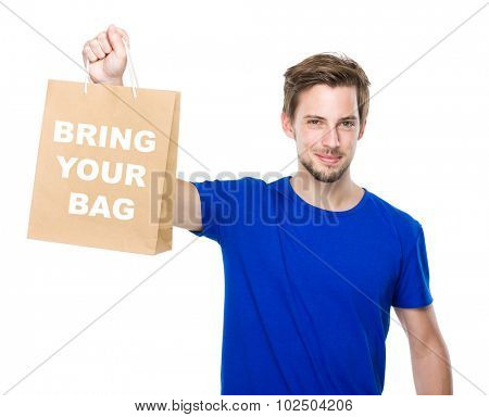 Young man hold with shopping bag and showing phrase bring your bag