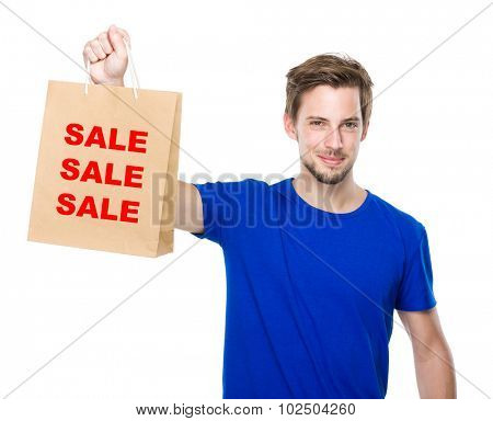 Young man hold with shopping bag and showing three words of sale