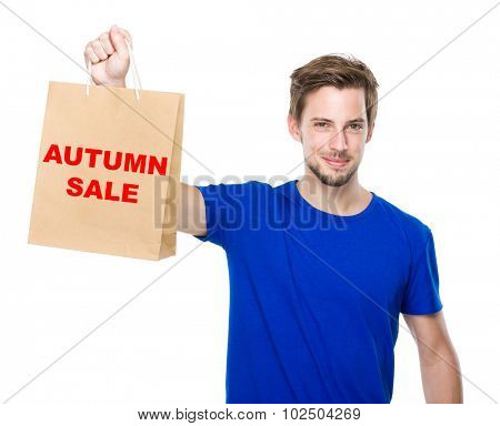 Young man hold with shopping bag and showing phrase autumn sale