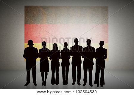 Silhouette of business people in a row against germany flag in grunge effect