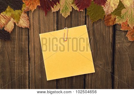 Orange adhesive note with a paperclip against autumn leaves on wood