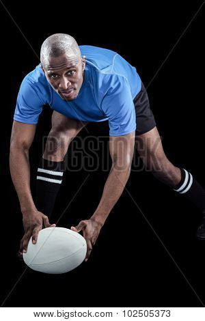 Portrait of sportsman bending and holding ball while playing rugby against black background