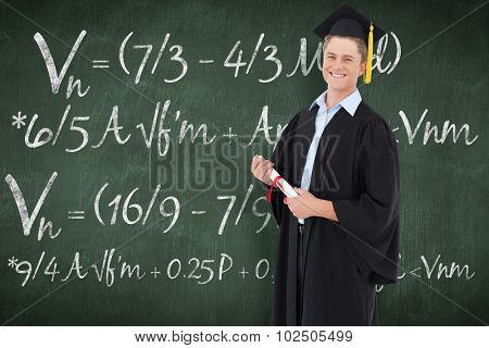 A smiling man looking at the camera as he graduates against green chalkboard