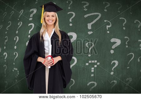 Smiling blonde student in graduate robe against green chalkboard