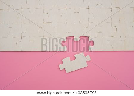 Jigsaw Puzzle With One Piece Loose On Pink Background