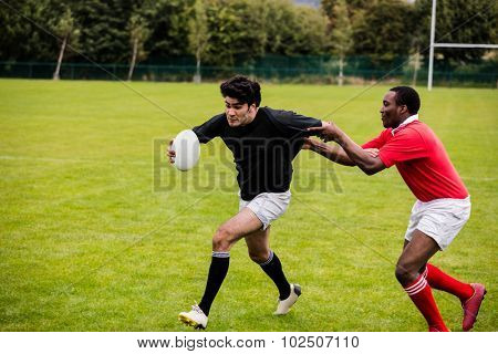 Rugby players tackling during game at the park