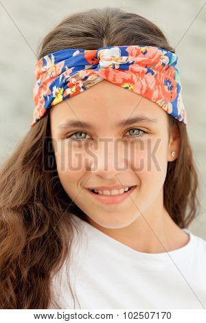 Pretty teenager girl with a flowered headband smiling