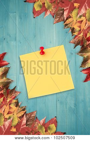 Illustrative image of pushpin on yellow paper against autumn leaves pattern