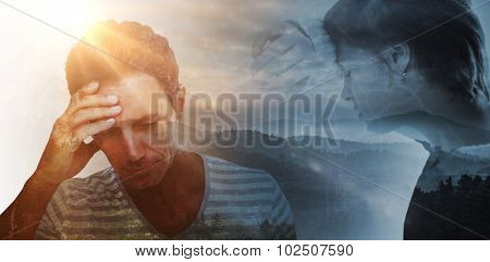 Sad pretty brunette leaning against wall against trees and mountain range against cloudy sky
