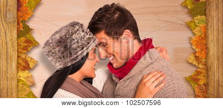 Young couple smiling and hugging against bleached wooden planks background