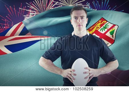 Rugby player with arms crossed against fireworks exploding over football stadium