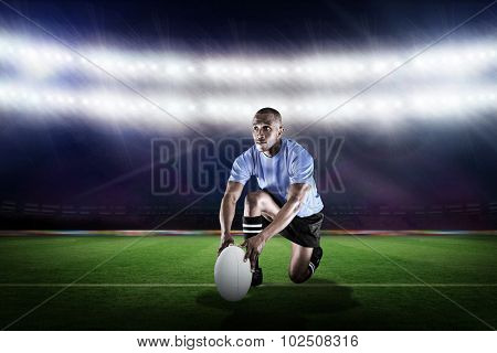 Rugby player holding ball while kneeling against rugby stadium