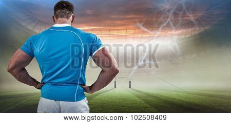 Rugby player with hands on hips against rugby pitch