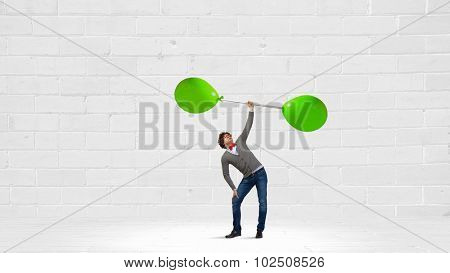 Confident guy lifting above head barbell with balloons