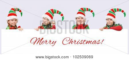 Four Girls In Suits Of Christmas Elf With Banner