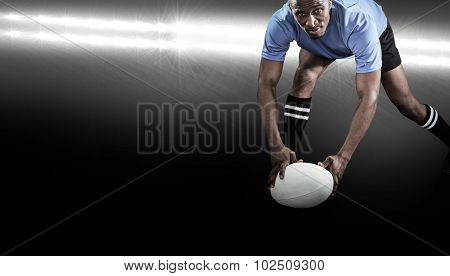 Portrait of sportsman bending and holding ball while playing rugby against spotlight