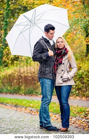 Couple enjoying fall day having walk despite the rain