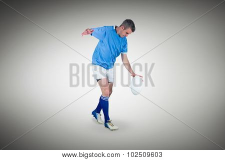 Rugby player kicking a rugby ball against grey vignette